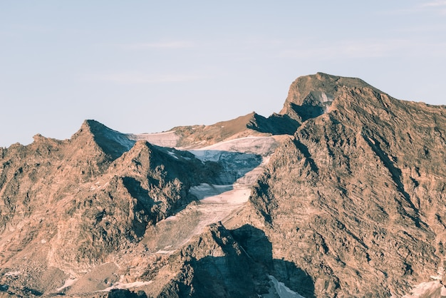 Sunset light over retiring dying glaciers on the italian french alps. climate change concept. toned desaturated image. Premium Photo