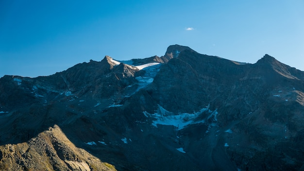 Sunset light over retiring dying glaciers on the italian french alps. climate change concept. Premium Photo