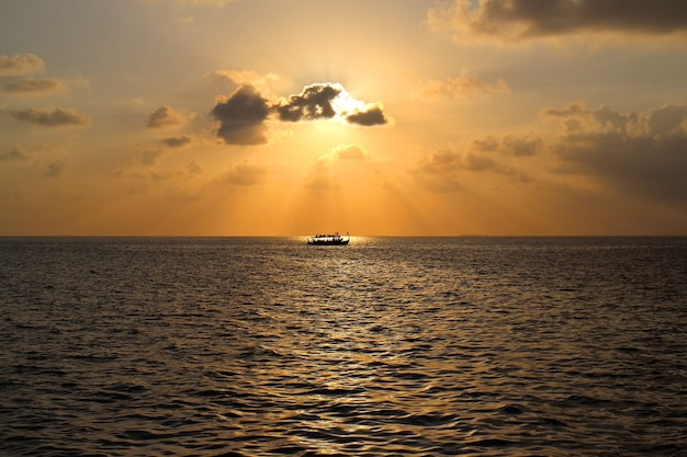 Sunset on maldives island with boat, view from water villas resort. Premium Photo