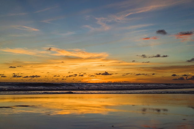 Sunset on the ocean. beautiful bright sky, reflection in water, waves. Free Photo
