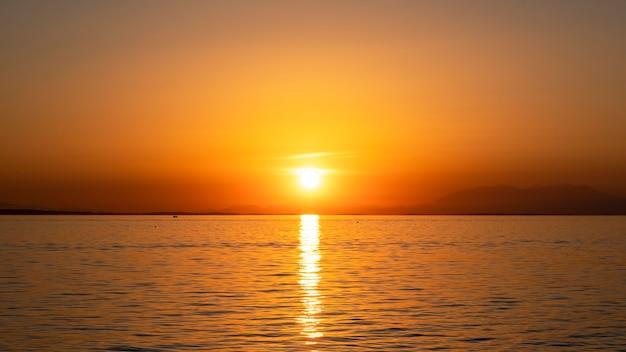 エーゲ海の海岸に沈む夕日、遠くに船と陸、水、ギリシャ 無料写真