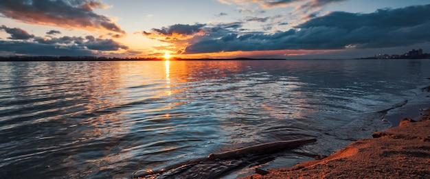 Закат на берегу реки. красивые облака, голубая газированная вода, упавшая ветка дерева в воде и песок на берегу оранжевого цвета от лучей заката. Premium Фотографии