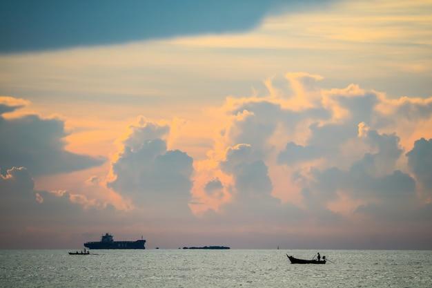 Закат оранжевого облака обратно на темном небе силуэта и рыбацкой лодке на море Premium Фотографии