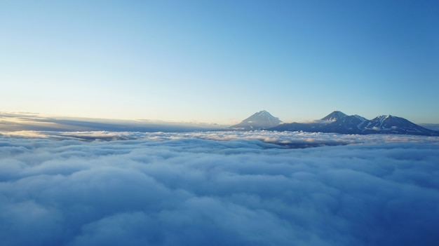 Sunset photo of kamchatka volcanoes. high altitude above clouds. shadows over cloud layer and mountains Premium Photo