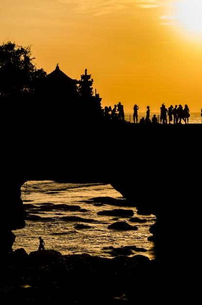 Sunset at pura batu bolong - tanah lot, bali , indonesia Premium Photo