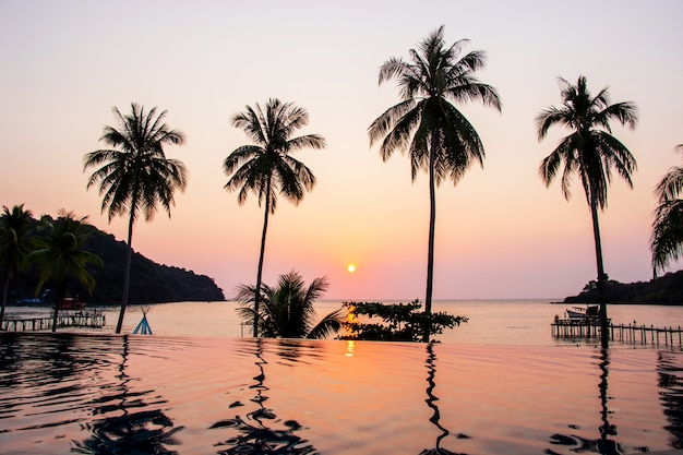 Sunset reflecting on the water surface foreground with coconut trees area ao bang bao Premium Photo