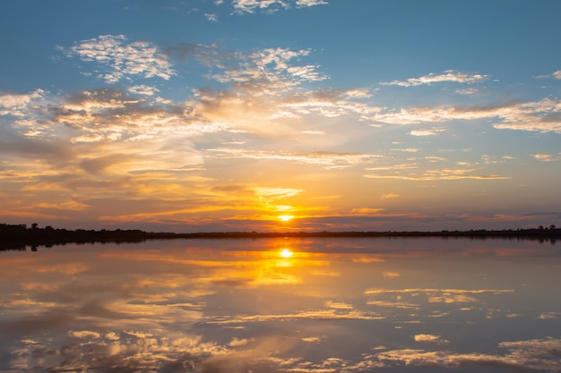 Sunset reflection lagoon. beautiful sunset behind the clouds and blue sky above the over lagoon landscape. dramatic sky with cloud at sunset Premium Photo