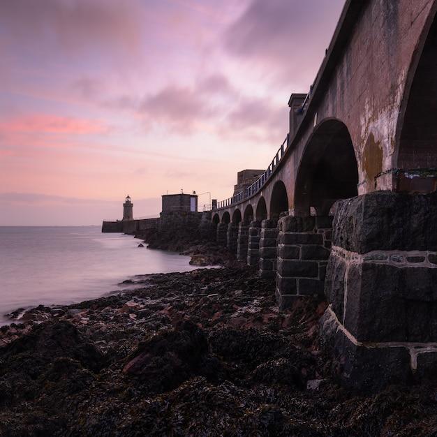 Tramonto nel cielo sopra il ponte e il faro vicino al mare a guernsey Foto Gratuite