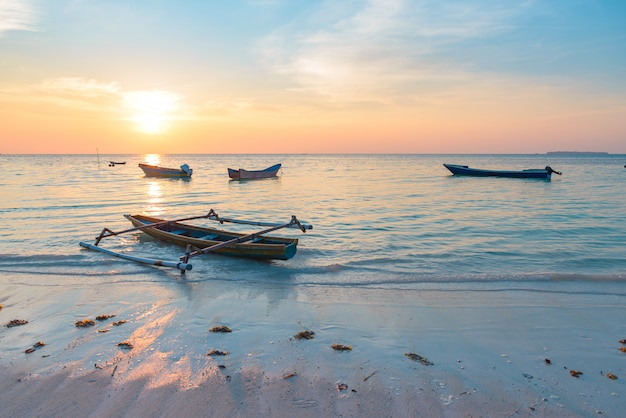 Sunset tropical beach caribbean sea wooden boats at pasir panjang Premium Photo