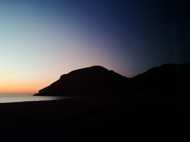 Sunset with a silhouette mountain on the beach Free Photo