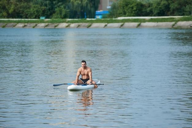 冷え、supボードの上に座って、都市湖の真ん中で泳いでいる男に合います。 Premium写真