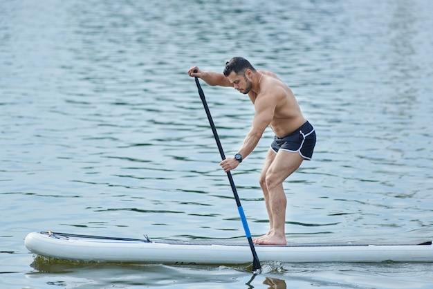 Взгляд со стороны тренировки человека с доской sup, кочуя с длинной лужицей в озере города. Premium Фотографии