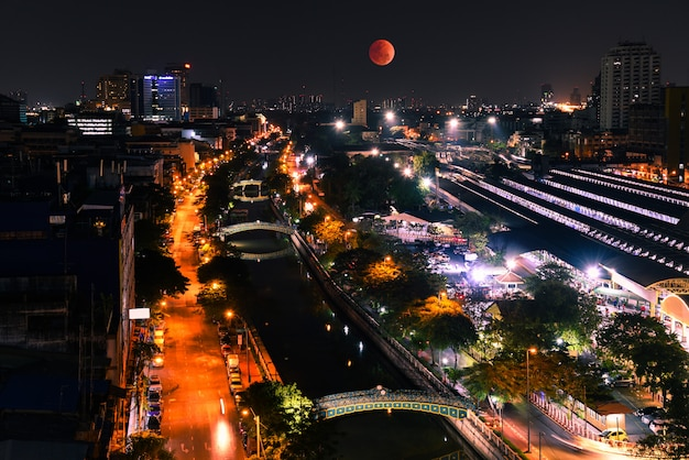 Super blood moon in the sky. with high angle view of bangkok at night. Premium Photo