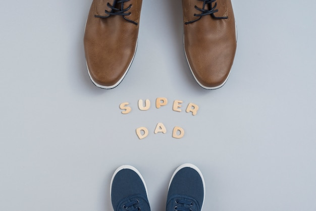 Super dad inscription with man and children shoes Free Photo