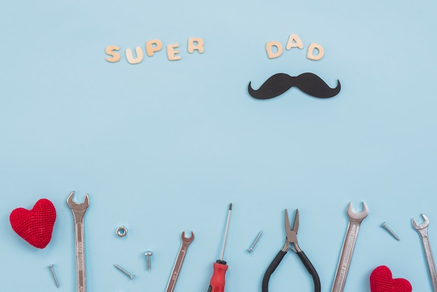 Super dad inscription with tools and paper mustache Free Photo