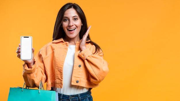 スマートフォンと買い物袋を持って超興奮した女性 無料写真