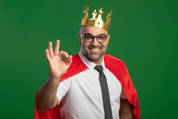 빨간 망토와 왕관을 쓰고 왕관을 쓰고있는 슈퍼 영웅 사업가 녹색 흰색 벽에 서있는 확인 서명을 유쾌하게 보여주는 웃고 무료 사진
