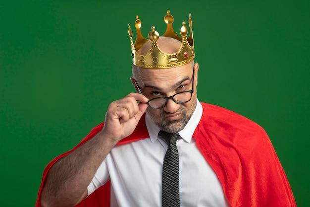 녹색 벽 위에 서있는 그의 안경을 만지고 카메라를 면밀히보고 왕관을 쓰고 빨간 망토와 안경에 슈퍼 영웅 사업가 무료 사진