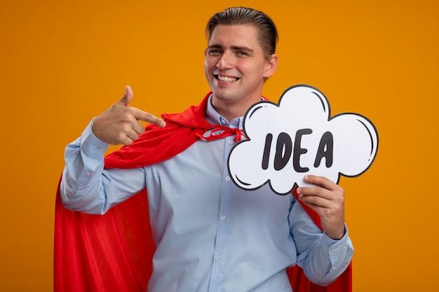 오렌지 배경 위에 서 웃 고 그것에 검지 손가락으로 가리키는 단어 아이디어와 연설 거품 기호를 들고 빨간 케이프에서 슈퍼 영웅 사업가 무료 사진