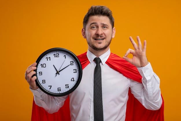 주황색 배경 위에 서있는 확인 표시를 유쾌하게 보여주는 카메라를보고 웃 고 벽 시계를 들고 빨간 케이프에서 슈퍼 영웅 사업가 무료 사진