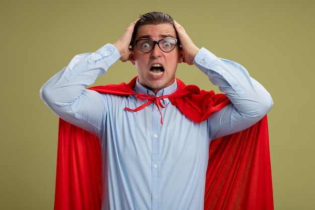 Super hero businessman in red cape and glasses looking at camera being crazy amazed and surprised touching his head standing over light background Free Photo