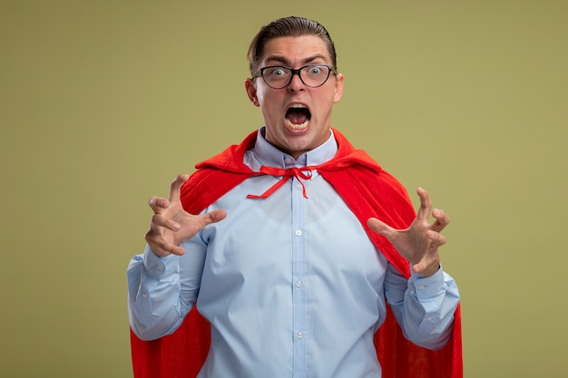 Super hero businessman in red cape and glasses shouting with raised hands crazy mad going wild standing over light background Free Photo