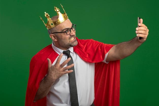 Uomo d'affari super eroe in mantello rosso e occhiali che indossa la corona facendo selfie utilizzando smartphone andando in piedi arrabbiato pazzo selvaggio sopra la parete verde Foto Gratuite