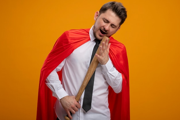 Super hero businessman in red cape holding baseball bat using as microphone singing standing over orange background Free Photo