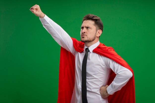 Super eroe uomo d'affari in mantello rosso tenendo la corona tenendo il braccio nel gesto di volo pronto a combattere in piedi su sfondo verde Foto Gratuite