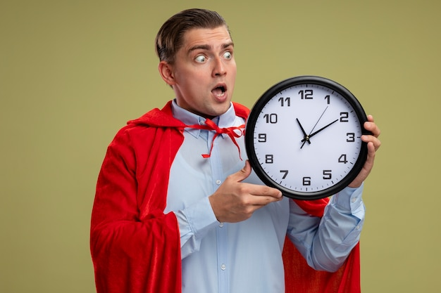 Super hero businessman in red cape holding wall clock looking at it being crazy amazed and surprised standing over light background Free Photo
