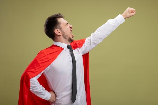 Uomo d'affari super eroe in mantello rosso tenendo il braccio nel gesto di volo gridando pronto a combattere in piedi su sfondo verde Foto Gratuite