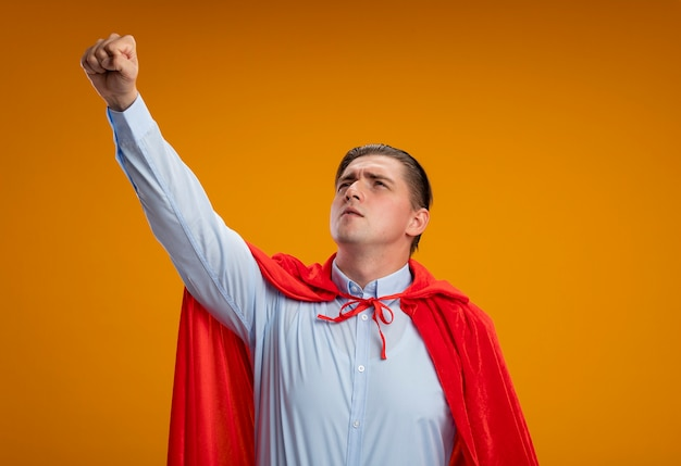 Uomo d'affari super eroe in mantello rosso che osserva da parte mantenendo il braccio nel gesto di volo in piedi su sfondo arancione Foto Gratuite