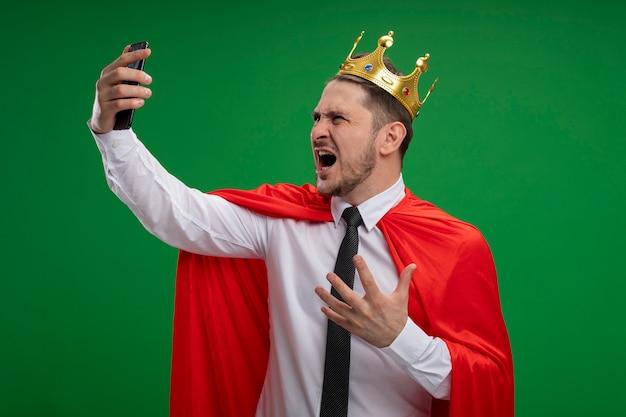 Super eroe imprenditore in mantello rosso che indossa la corona facendo selfie utilizzando lo smartphone impazzendo in piedi arrabbiato selvaggio su sfondo verde Foto Gratuite