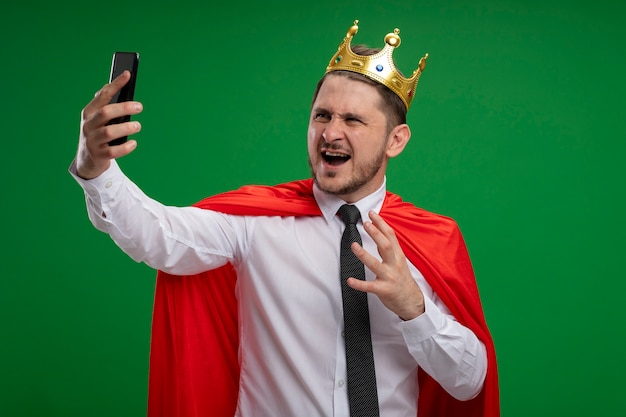 Super hero businessman in red cape wearing crown doing selfie using smartphone going wild crazy angry standing over green background Free Photo