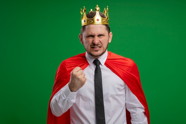 Super hero businessman in red cape wearing crown looking at camera with angry face clenching fist standing over green background Free Photo