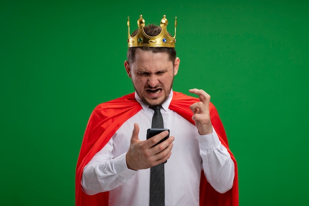 Super hero businessman in red cape wearing crown using smartphone going wild crazy angry standing over green background Free Photo