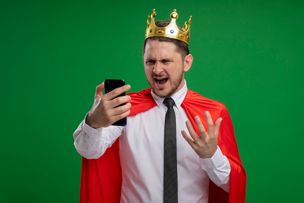 Super hero businessman in red cape wearing crown using smartphone looking at screen going wild crazy angry standing over green background Free Photo