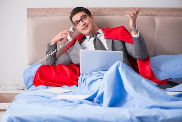 Super hero businesswoman working in bed Premium Photo