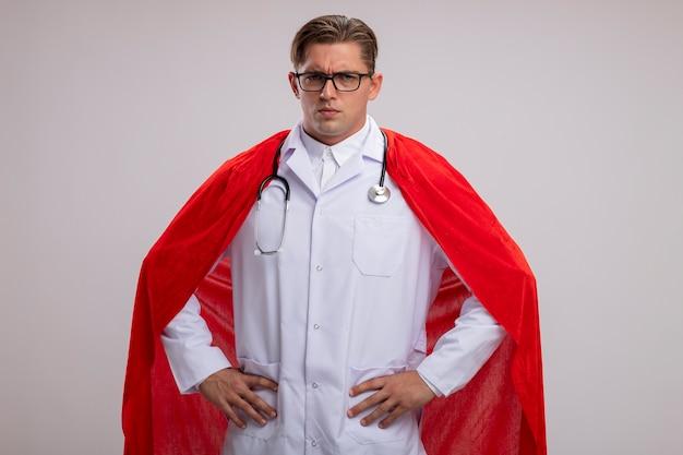 白い背景の上に立っている腰に腕で真剣に自信を持って表情でカメラを見て首の周りに聴診器で白いマントとガラスの白いコートを着ているスーパーヒーロードクター男 無料写真