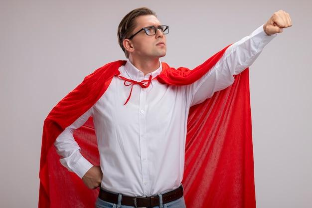 Uomo super eroe in mantello rosso e occhiali che osserva da parte con la faccia seria che fa il gesto vincente con la mano pronta ad aiutare in piedi sul muro bianco Foto Gratuite