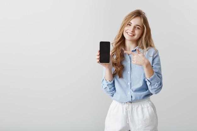 Супер полезное устройство. довольная симпатичная студентка со светлыми волосами, в рубашке с синим воротником, демонстрирующая черный смарфтон и указывающая на гаджет указательным пальцем, предлагающая купить предмет Бесплатные Фотографии