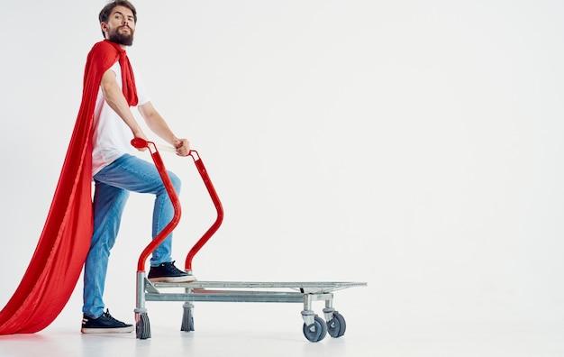 A superhero in a red cloak stands on a cargo cart in a bright room Premium Photo