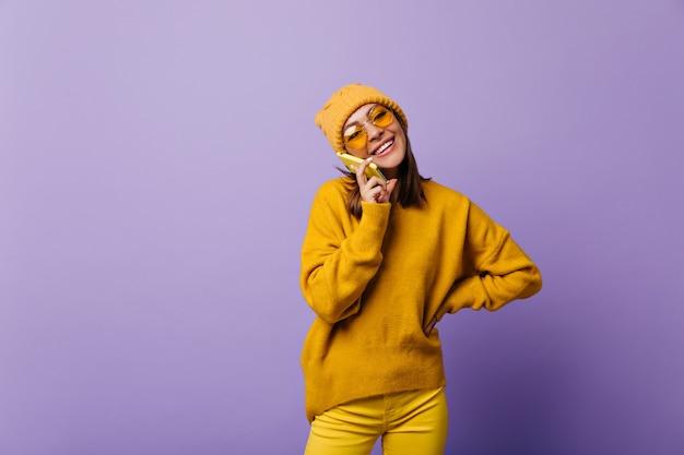 Превосходная замечательная активная девушка в желтом total look с веселым настроением разговаривает по телефону. портрет 24-летней модели Бесплатные Фотографии