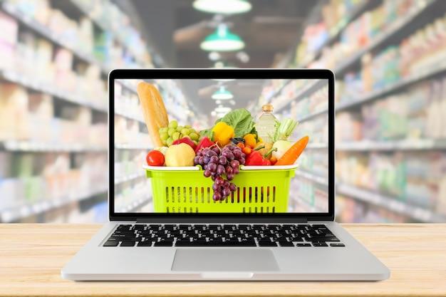 スーパーマーケットの通路には、ラップトップコンピューターと木製のテーブルの食料品の買い物かごの背景がぼやけ Premium写真