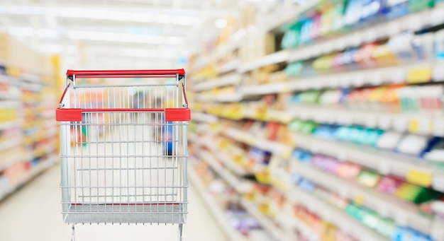 空の赤いショッピングカートのあるスーパーマーケットの通路 Premium写真