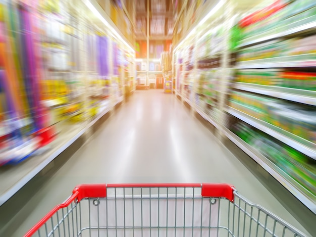 Supermarket aisle with empty red shopping cart Premium Photo