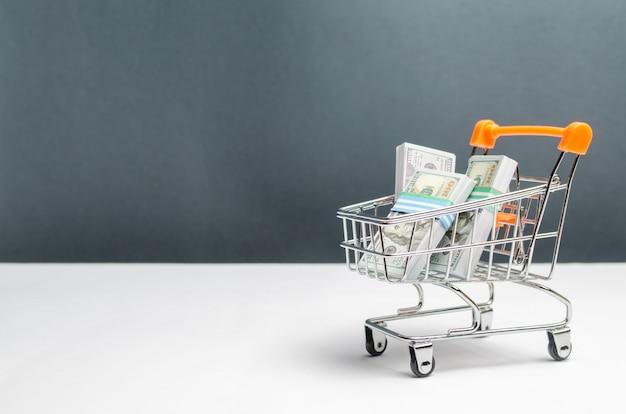 Supermarket cart with packs of dollars Premium Photo