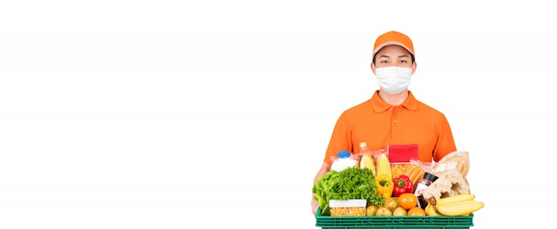 Supermarket delivery man wearing medical mask while holding food and groceries basket isolated Premium Photo