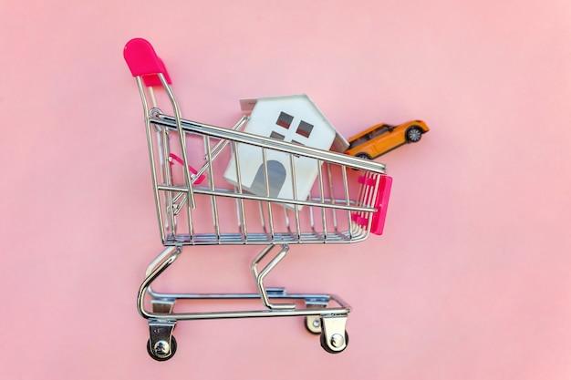 분홍색 테이블에 장난감 백악관 및 자동차 쇼핑 슈퍼마켓 식료품 푸시 카트 프리미엄 사진