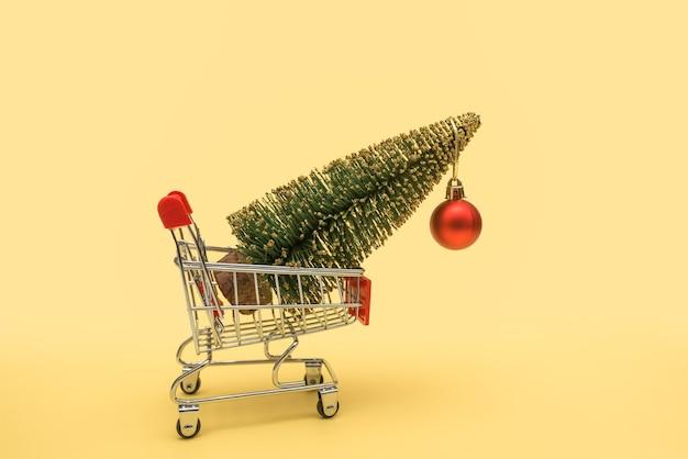 赤いボールで飾られたバスケットにクリスマスツリーが付いたスーパーマーケットのトロリー。 Premium写真
